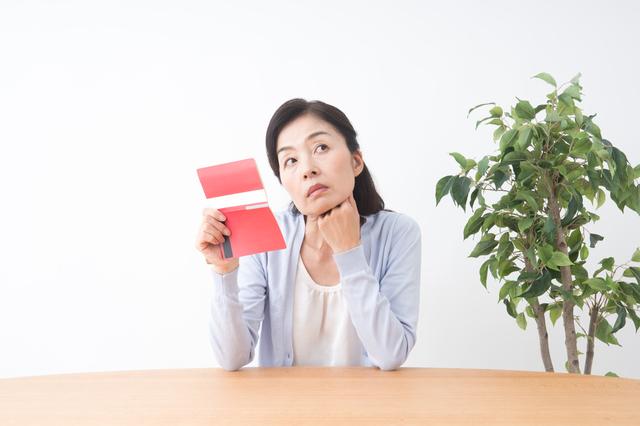 通帳を持って考える女性