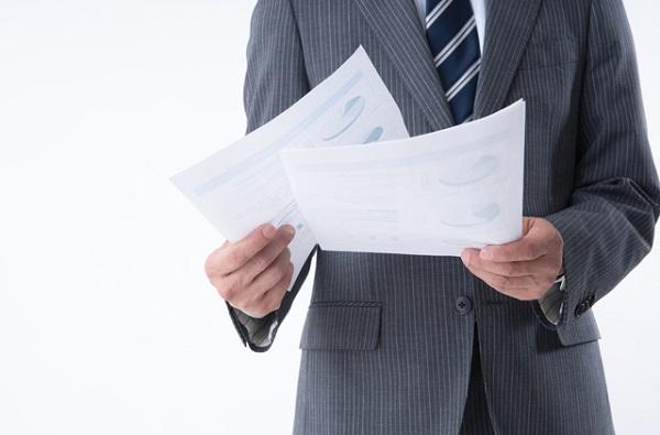 必要書類を持つスーツ姿の人