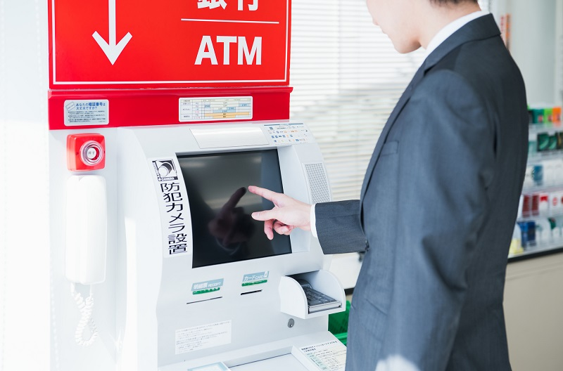ATMを操作する男性