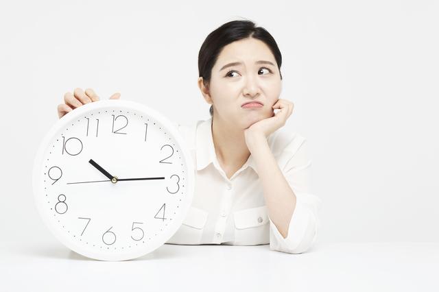 壁掛け時計と女性